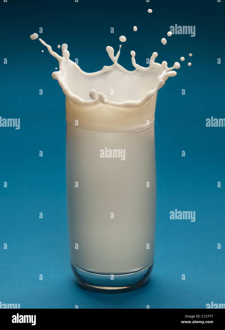 Spritzer Milch aus dem Glas auf blauem Hintergrund Stockbild