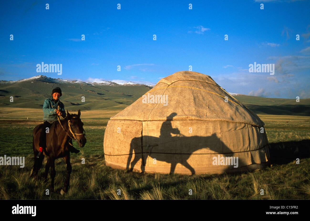 Pferd und Reiter vor einer Jurte, Verein‑ zu Mountain Range, Song-Kul, Kirgisien, Zentralasien Stockfoto