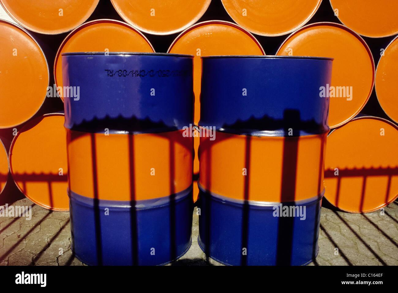 Zwei aufrechte Ölfässer malte zwei Farben stehen vor einer Reihe von gestapelte Ölfässer Stockbild