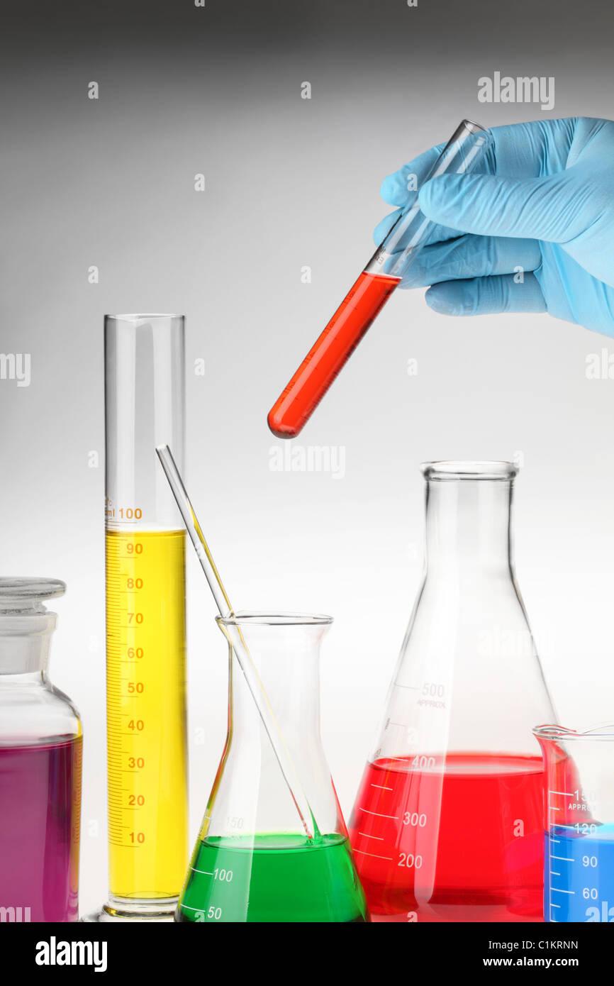 Hand hält Reagenzglas unter Labor-Glaswaren Stockbild