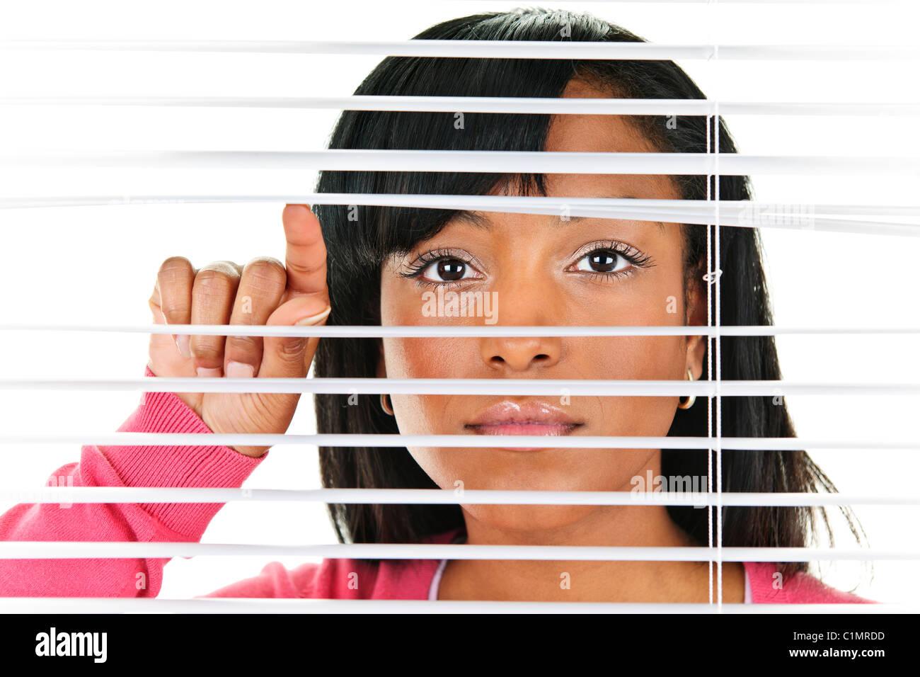 Junge schwarze Frau, die durch horizontale Jalousien Stockbild