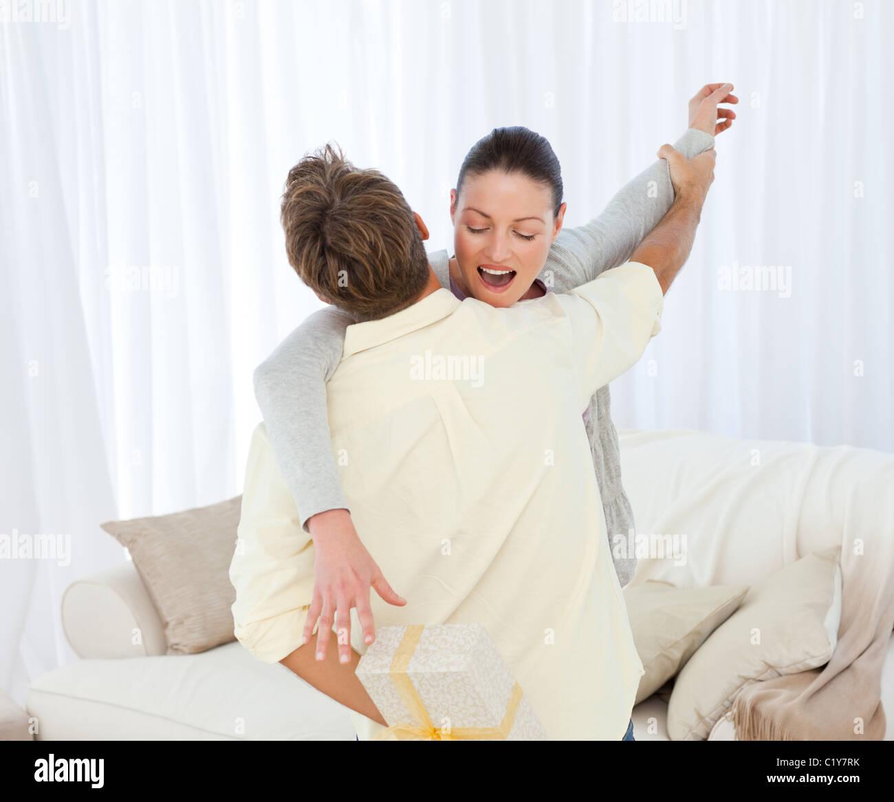 Erregte Frau Fang ein Geschenk versteckt hinter ihrem Freund Stockbild