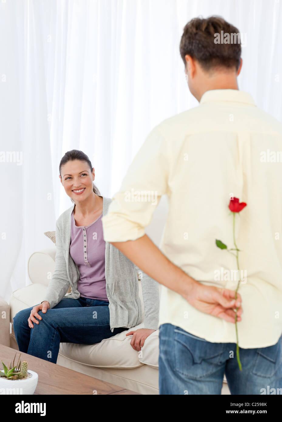 Leidenschaftlicher Mann versteckt für seine Freundin eine Rose hinter seinem Rücken Stockbild