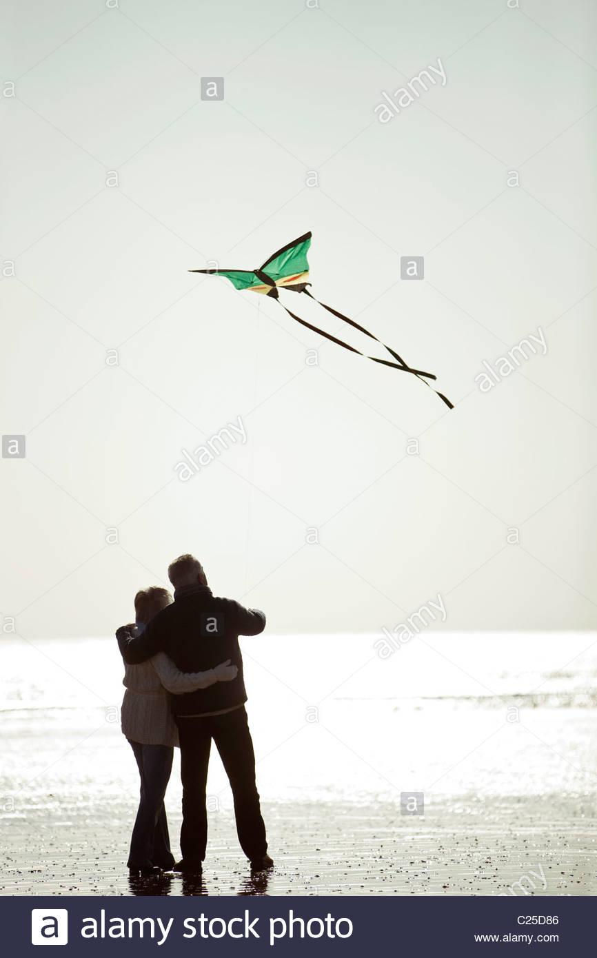 Ein älteres paar Drachen am Strand, Rückansicht Stockfoto