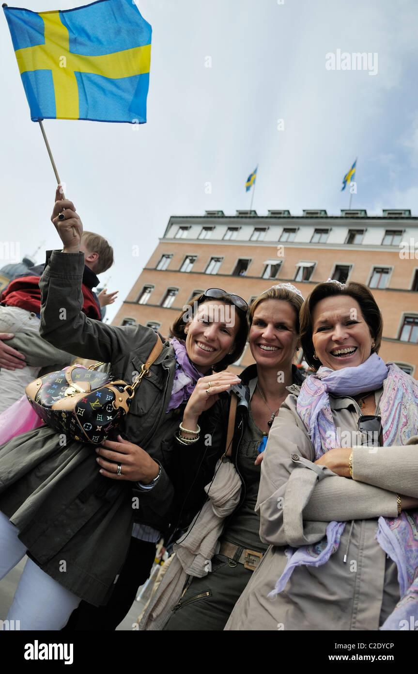 Drei Frauen mittleren Alters, Lächeln und winken kleine schwedische Flagge während der königlichen Stockbild