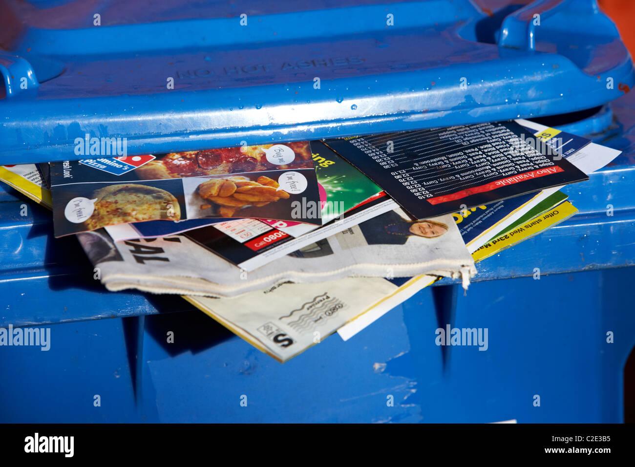blaues Papier recycling Behälter mit Junk-Mail und lokale Zeitungen kleben aus ihm heraus und Deckel nicht Stockbild