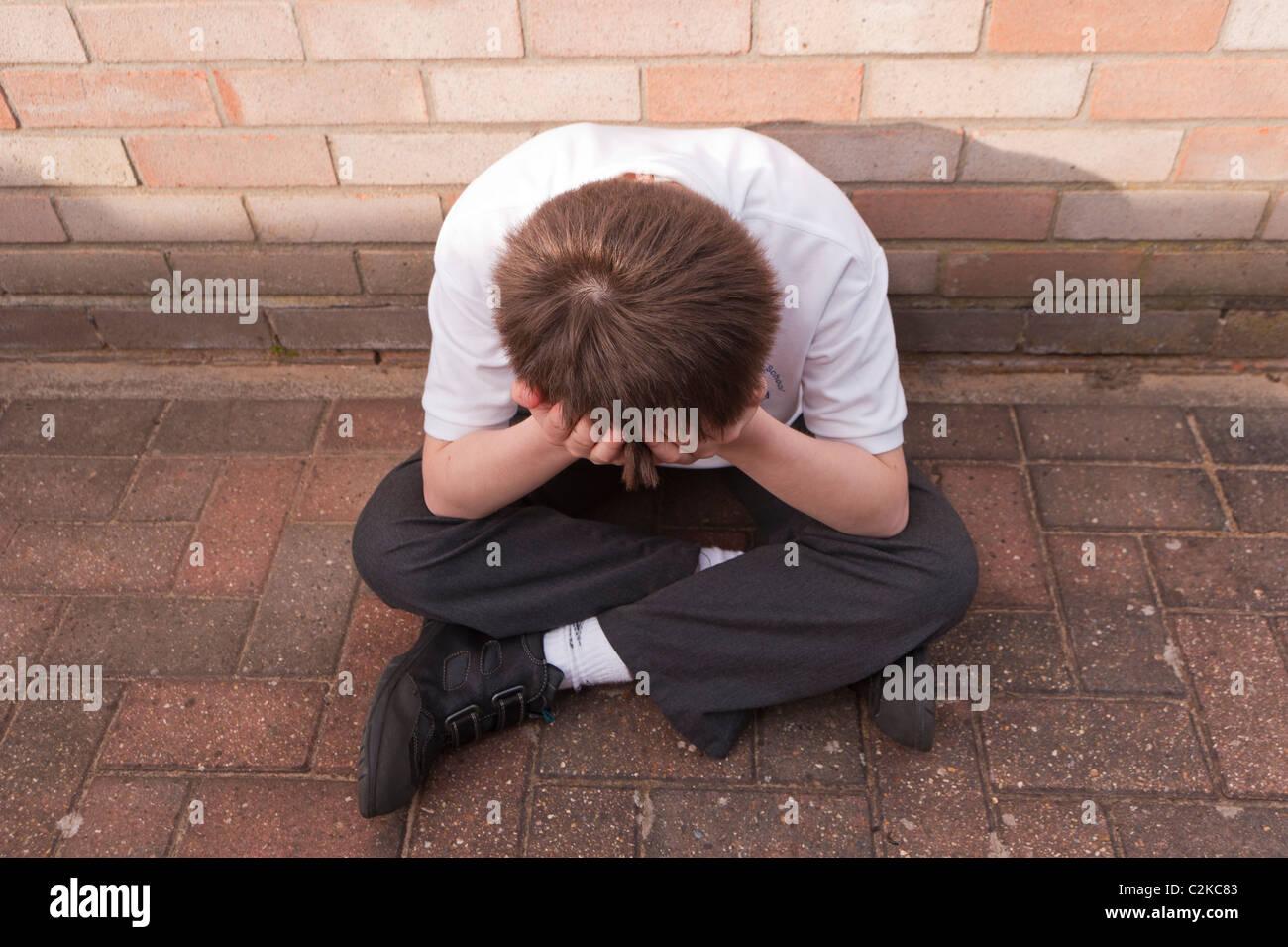 Ein MODEL Release Bild eines elf Jahre alten Jungen auf der Suche deprimiert im Freien tragen seine Schuluniform Stockbild