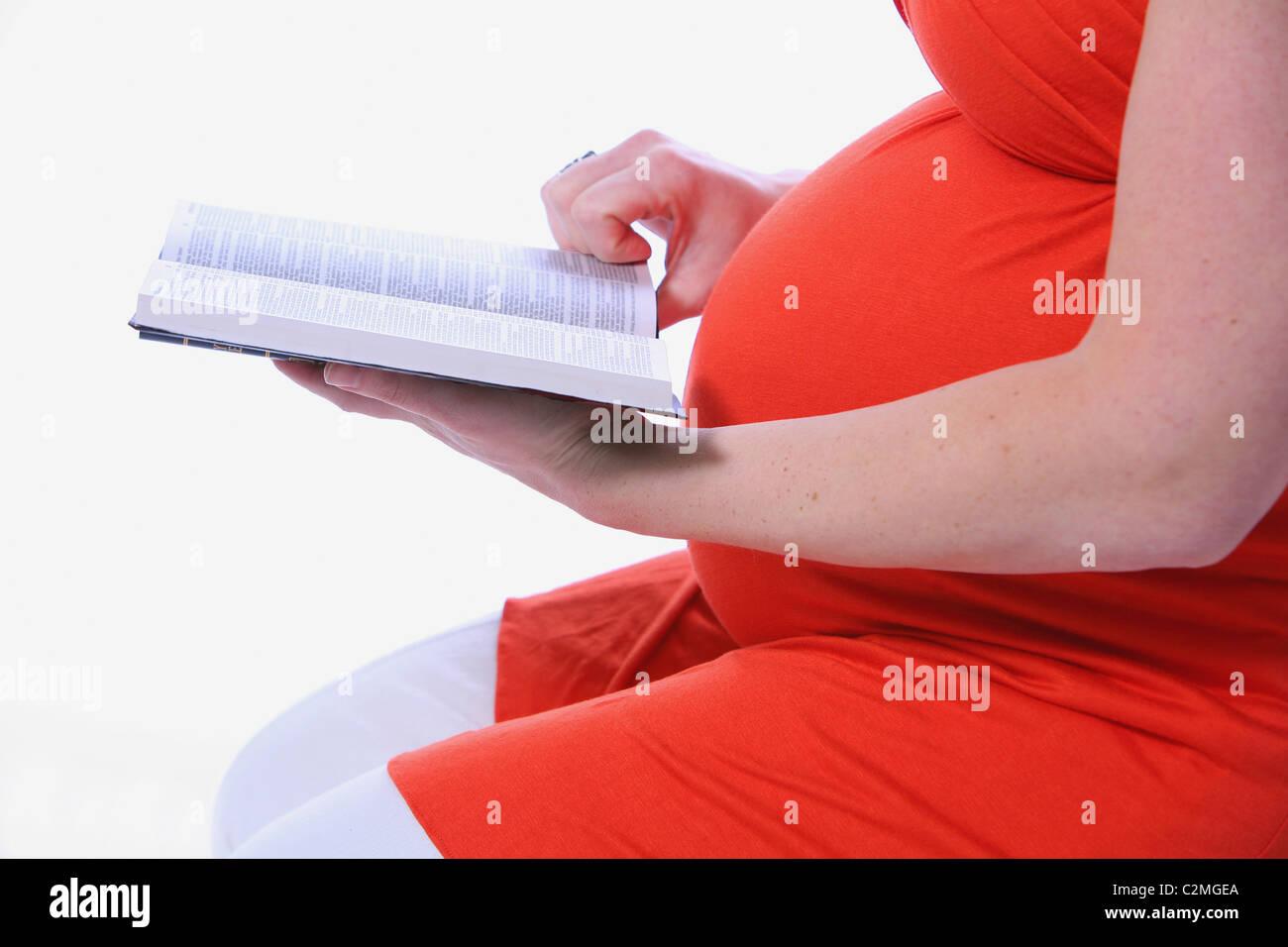 Schwangere Frau, ein Buch zu lesen Stockbild