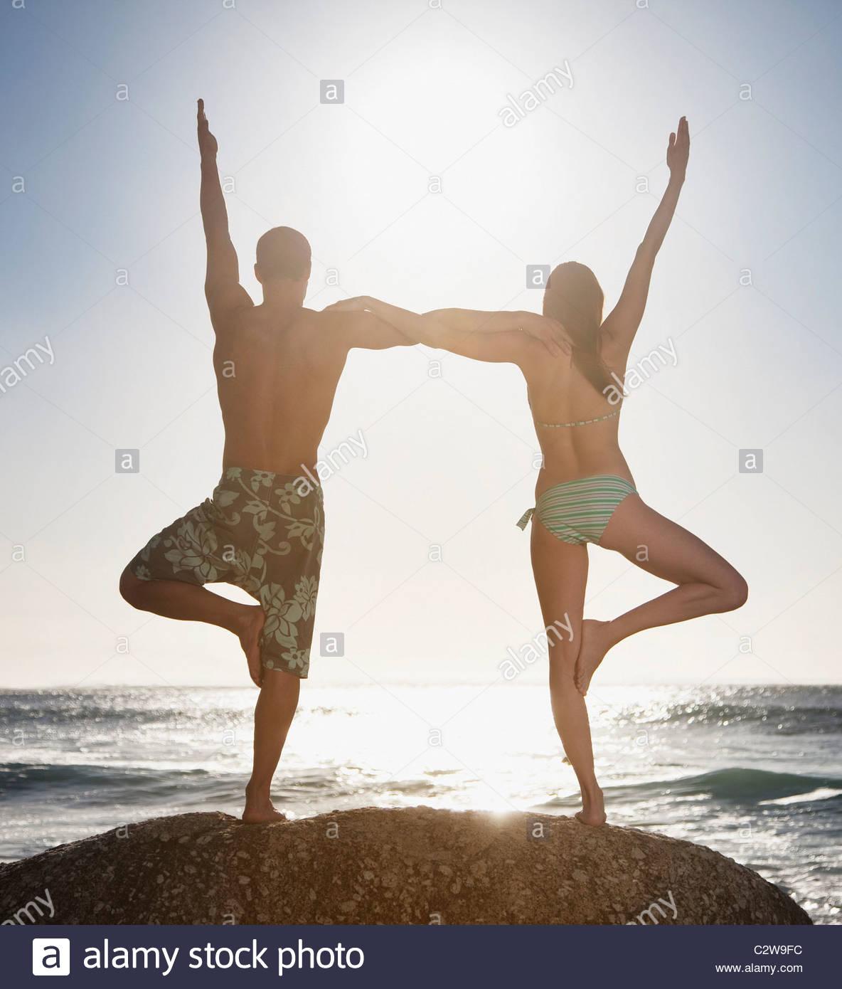 Paar, balancieren auf einem Bein zusammen am Strand Stockbild