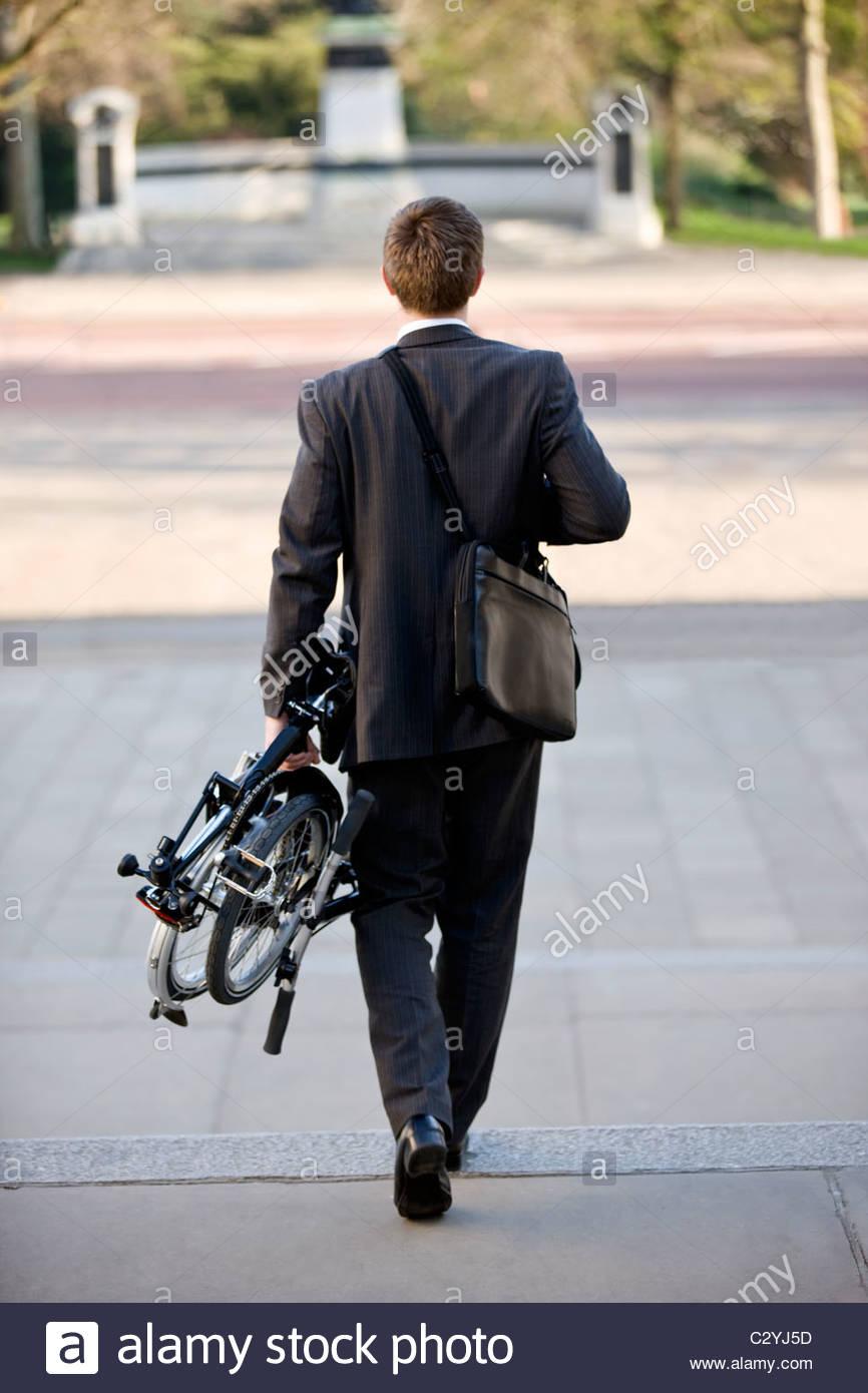 Ein Geschäftsmann mit seinem gefalteten Fahrrad zu arbeiten Stockbild