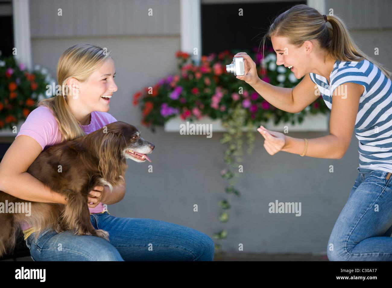 Teen Mädchen posiert mit ihrem Hund während bester Freund Foto mit Digitalkamera nimmt Stockbild