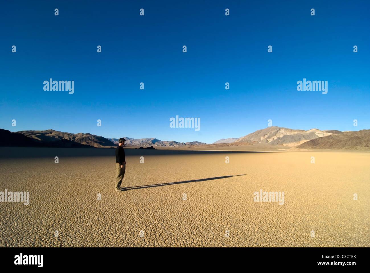 Ein Mann steht auf der Rennstrecke Blick auf seinen langen Schatten auf dem Sand in Death Valley Nationalpark, CA. Stockbild