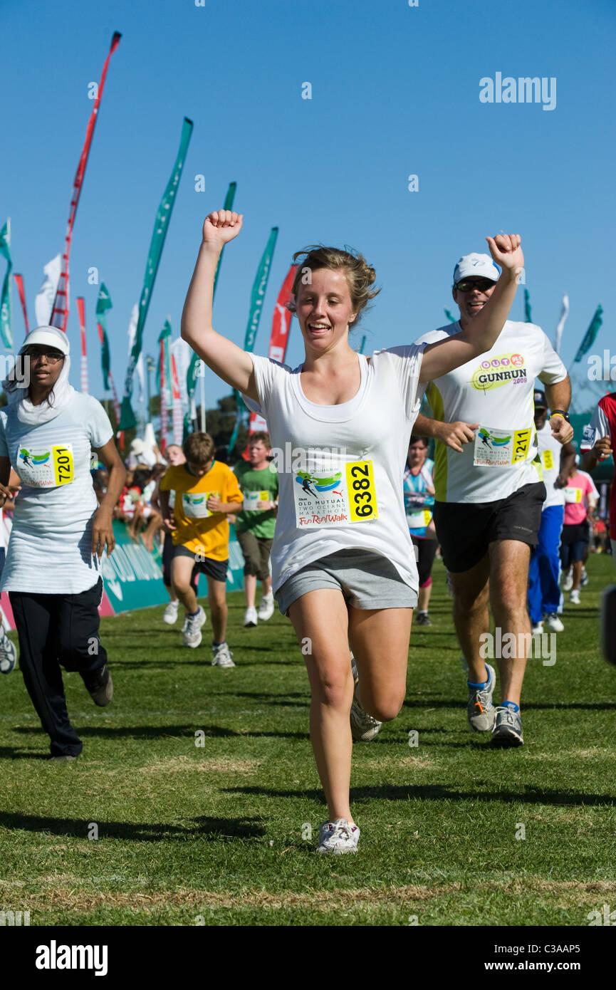 Läufer feiert am Ende der 5km Fun Run, zwei Ozeane Marathon, Kapstadt, Südafrika Stockbild