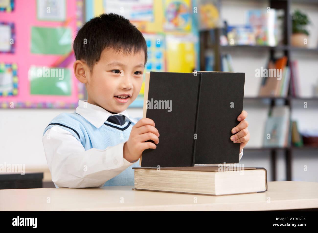Junger Student lesen im Klassenzimmer Stockbild
