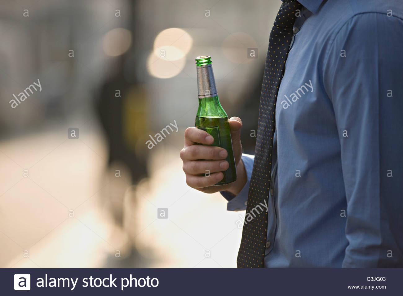 Ein Geschäftsmann mit einer Flasche Bier Stockbild