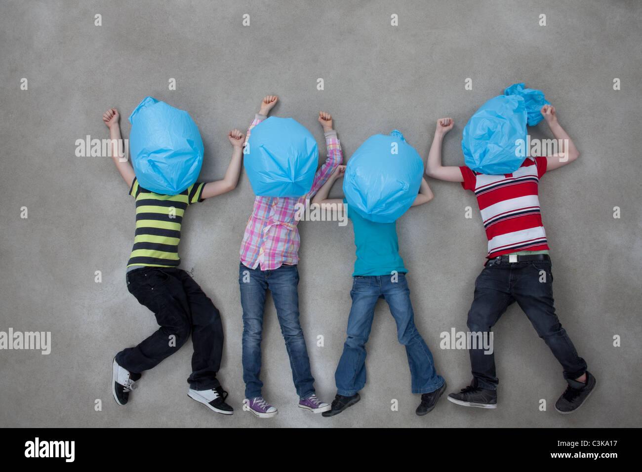 Leute für ihre Gesichter mit Plastiktüten und Ökologie Symbol zeigt Stockbild
