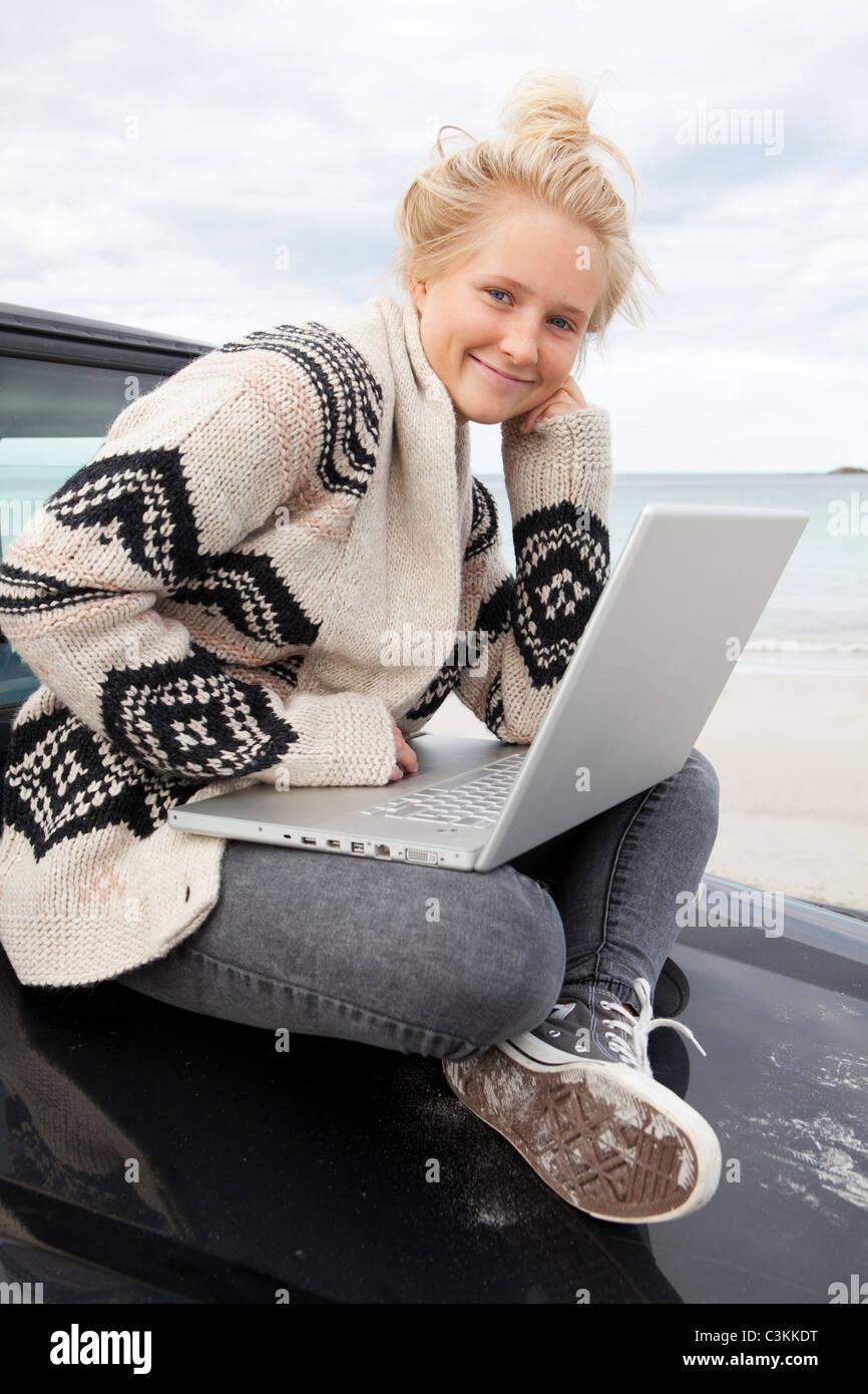 Teenager-Mädchen sitzen auf Geländewagen, mit Laptop, Lächeln, Porträt Stockbild