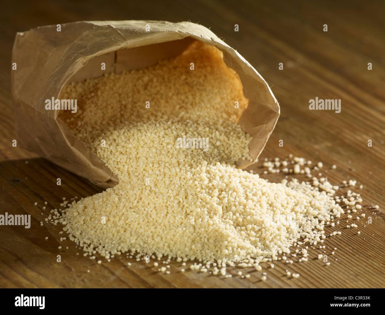 Couscous, Verschütten auf Holzuntergrund Stockbild
