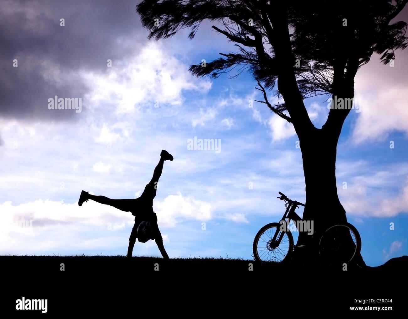 Die Silhouette der Mountainbiker mit Handstand auf dem Hügel Stockbild