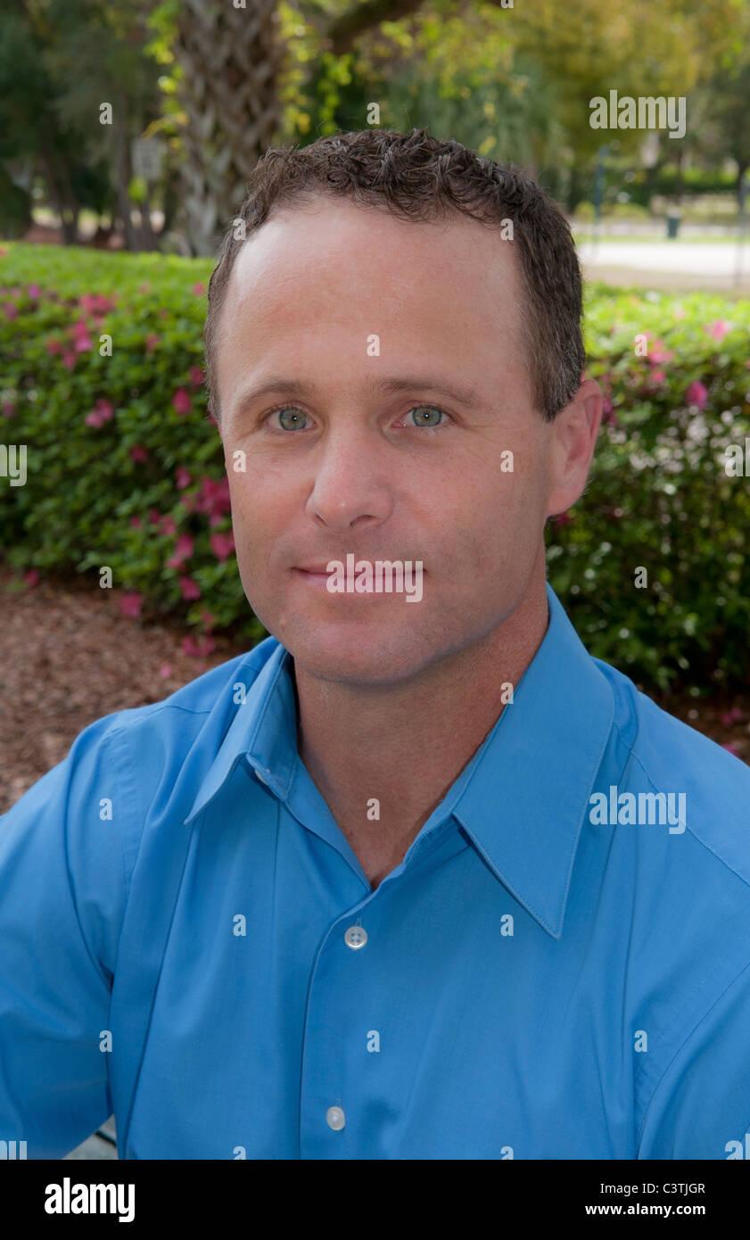 Porträt des Mannes im Alter von 30 Sekunden im Freien im Park mit blauem Hemd Stockbild