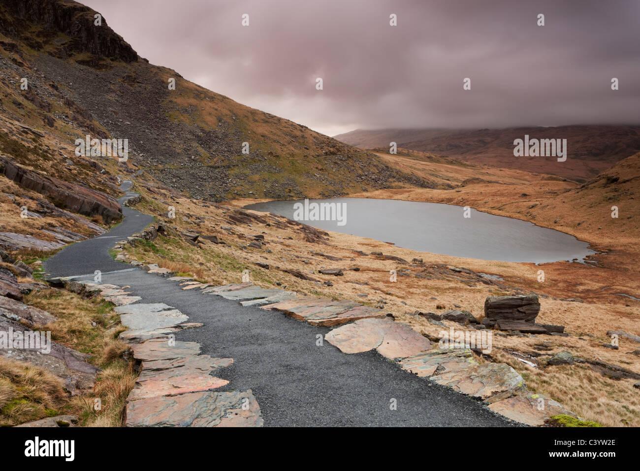 Der Bergarbeiter Track Fußweg Wicklung um Llyn Teyrn auf der Abfahrt vom Mount Snowdon in Snowdonia Stockbild
