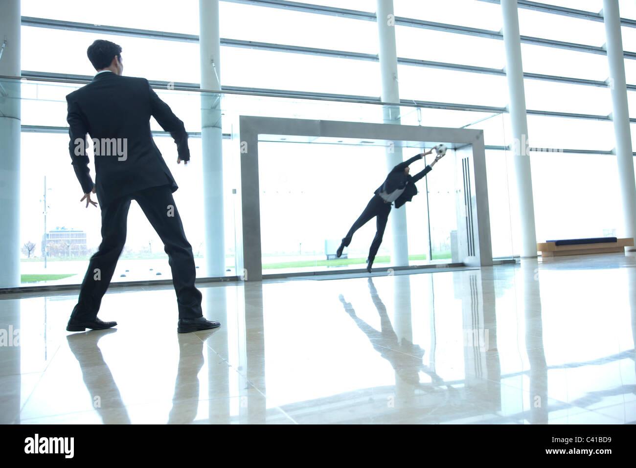 Geschäftsleute, die Fußballspielen in lobby Stockbild