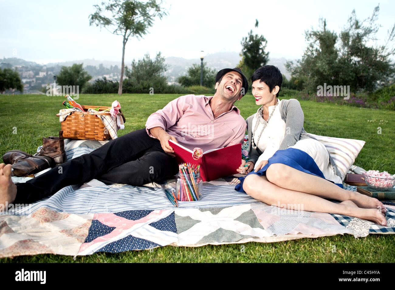 Barfuß, stilvolles Paar entspannen und Picknicken auf einer üppigen grünen Rasen eines Parks. Der Stockbild