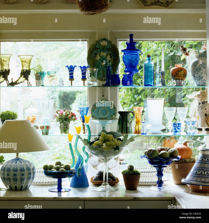 Sammlung von sortierten Glaswaren auf Fenster-Regale Stockbild