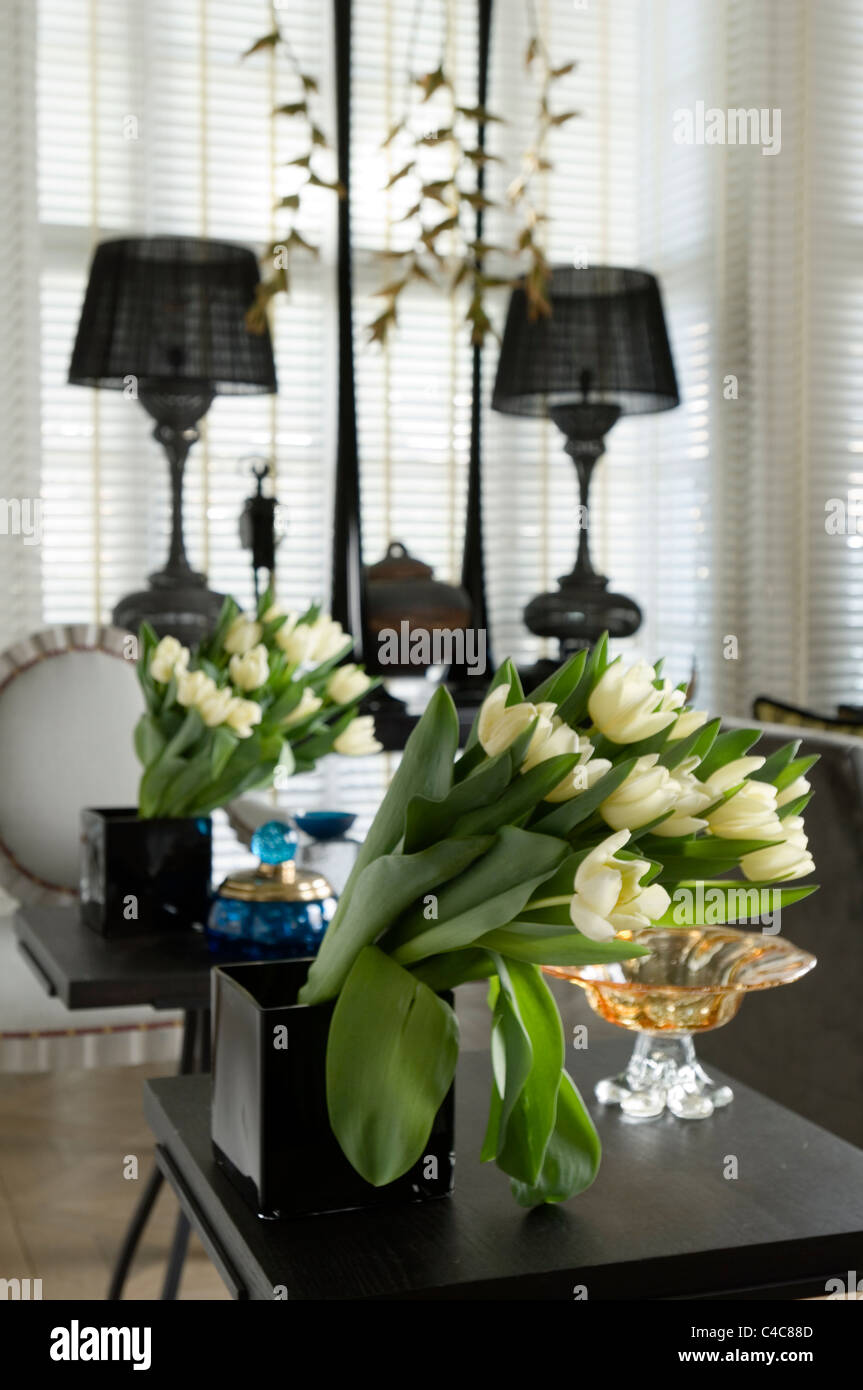 Reihe von Tulpen in einer schwarzen quadratischen Vase mit Spiegelbild Stockbild