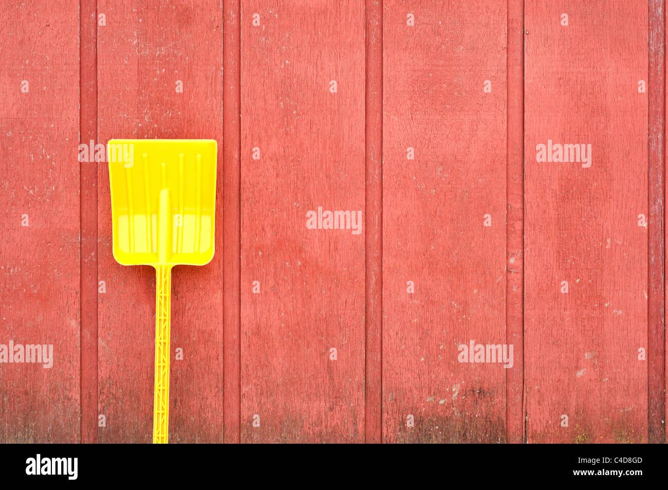 Eine gelbe Plastikspielzeug Schaufel lehnt sich an eine rote Scheune aus Holz Wand Stockbild