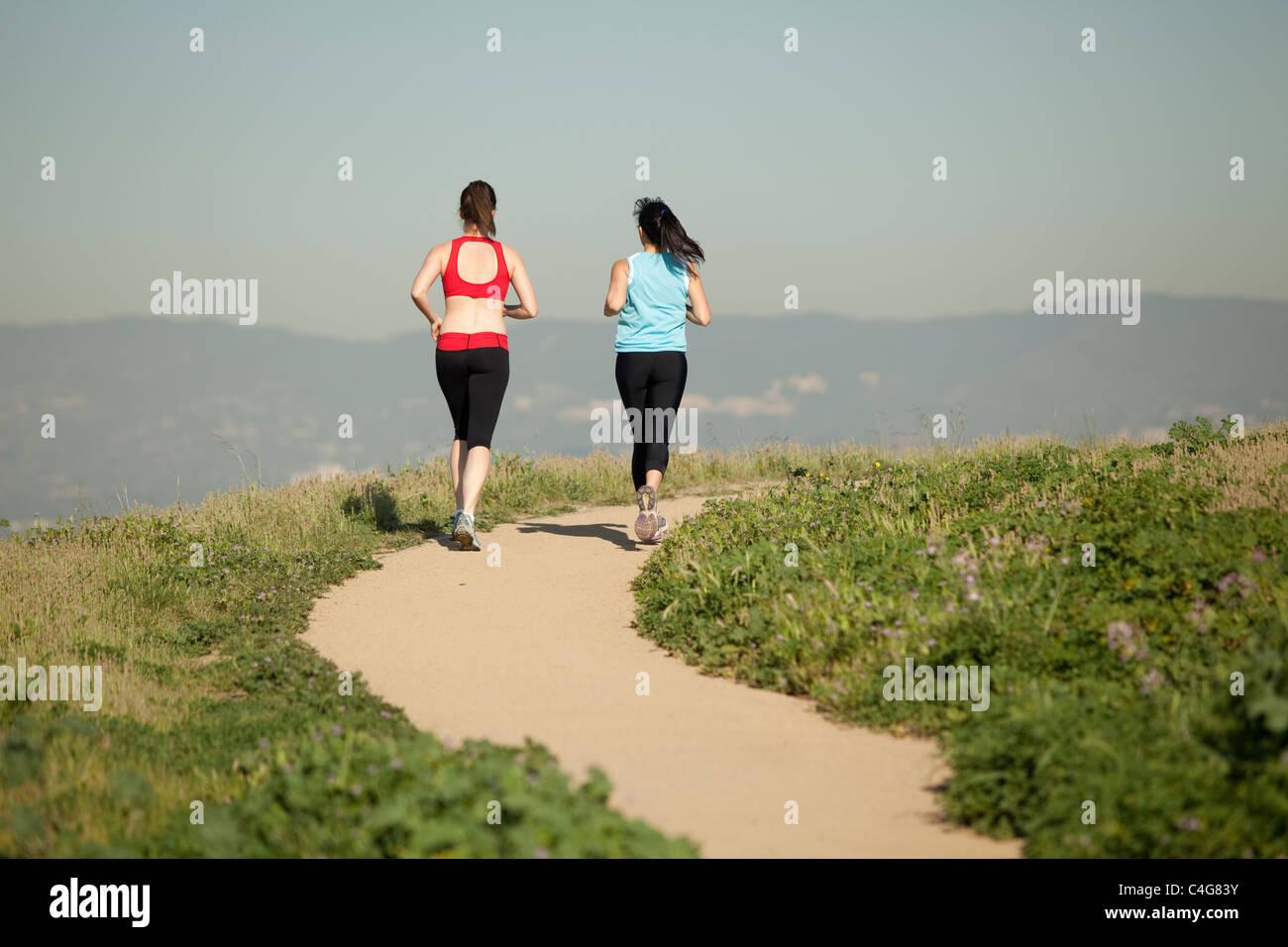 zwei sportliche Frauen in Trainingskleidung, läuft auf einer unbefestigten Weg durch die Natur in der Tageszeit Stockbild