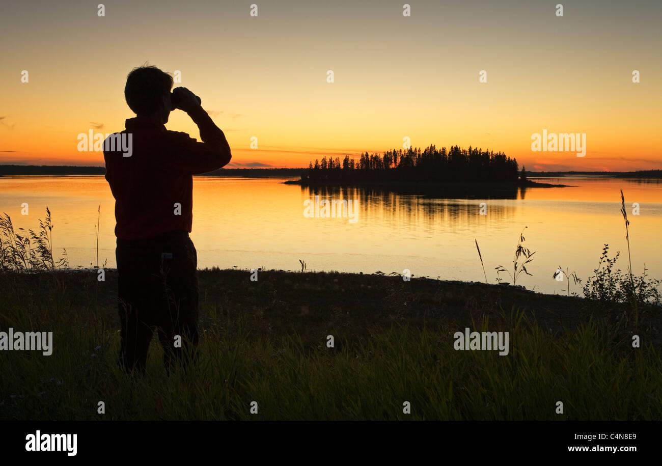 Mittleren Alters männlichen Wanderer Blick auf Astotin Lake mit dem Fernglas in der Abenddämmerung, Elk Stockbild