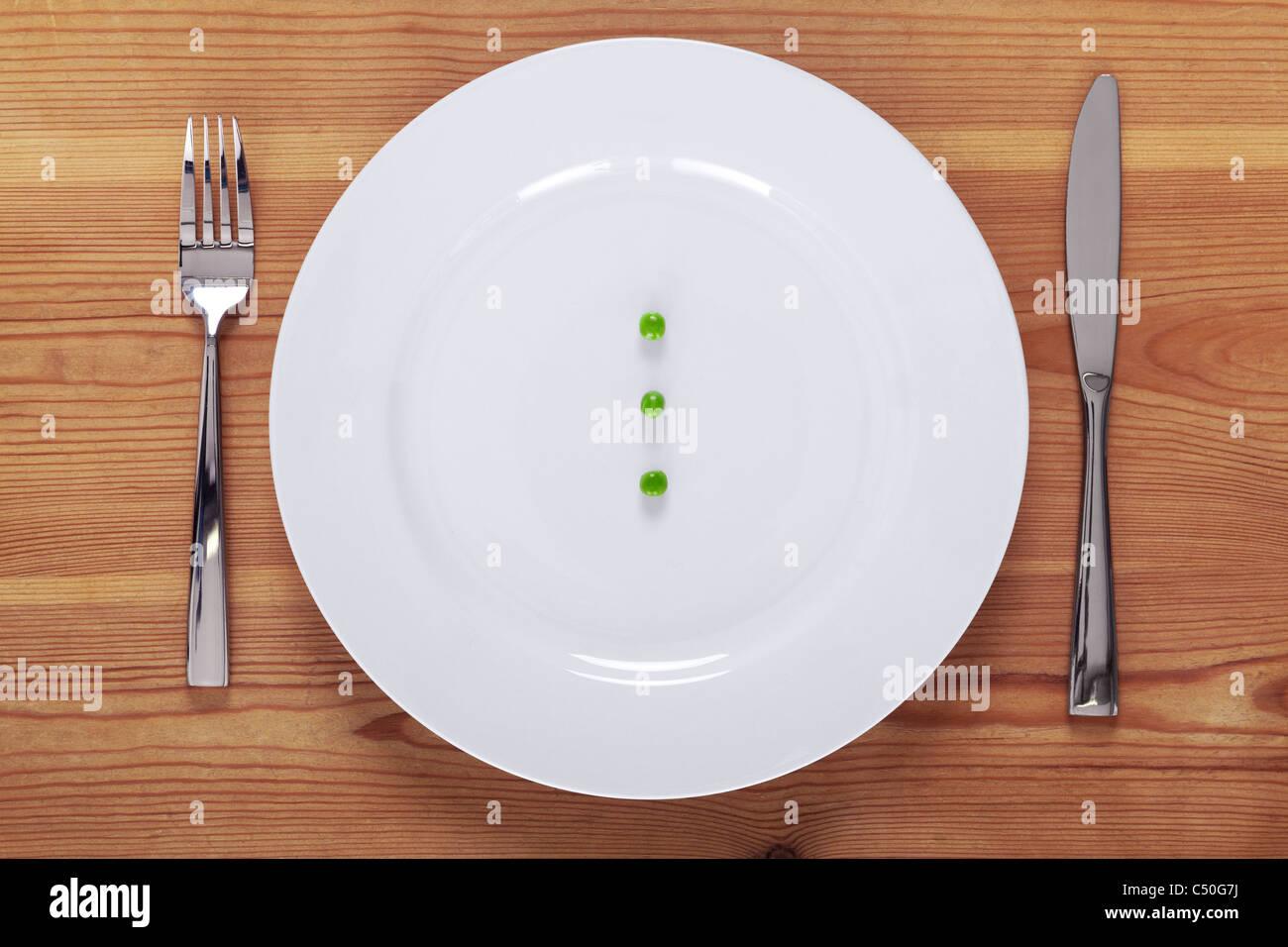 Foto von drei grüne Erbsen auf einem weißen Teller mit Messer und Gabel auf einem rustikalen Holztisch. Stockbild