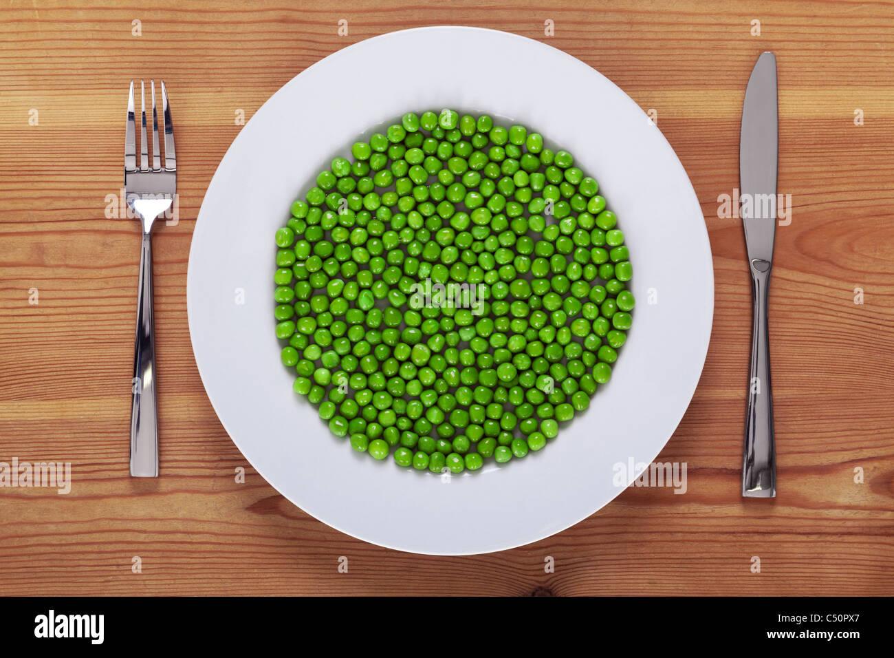 Foto von grünen Erbsen auf einem weißen Teller mit Messer und Gabel auf einem rustikalen Holztisch. Stockbild