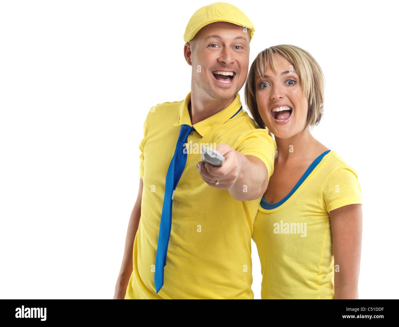 Junges Paar mit einer TV-Fernbedienung zu lachen. Isoliert auf weißem Hintergrund. Stockbild