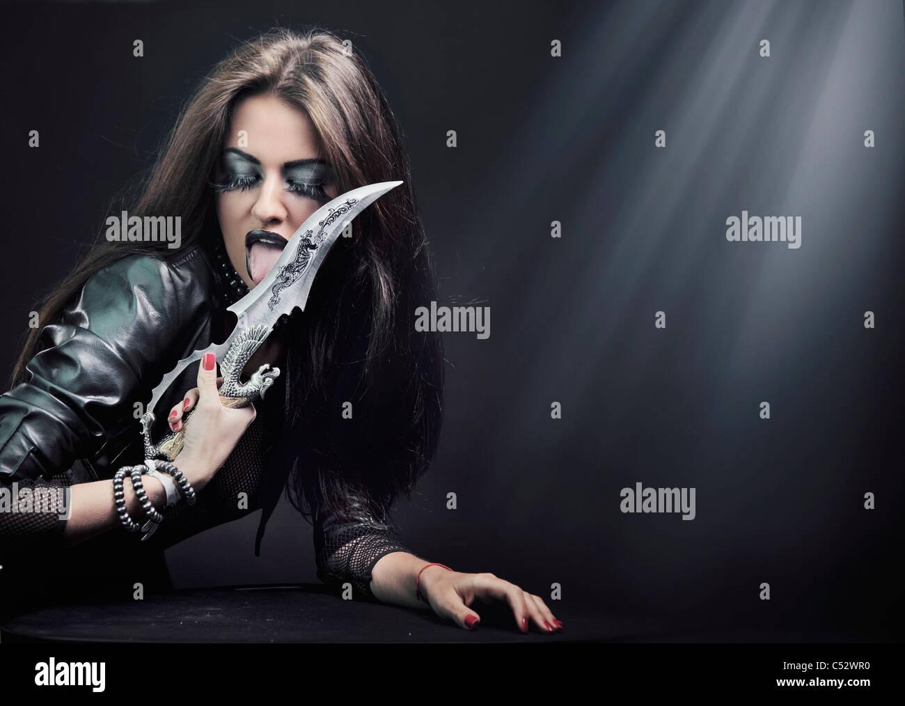 Attraktive junge Frau mit Messer Stockbild