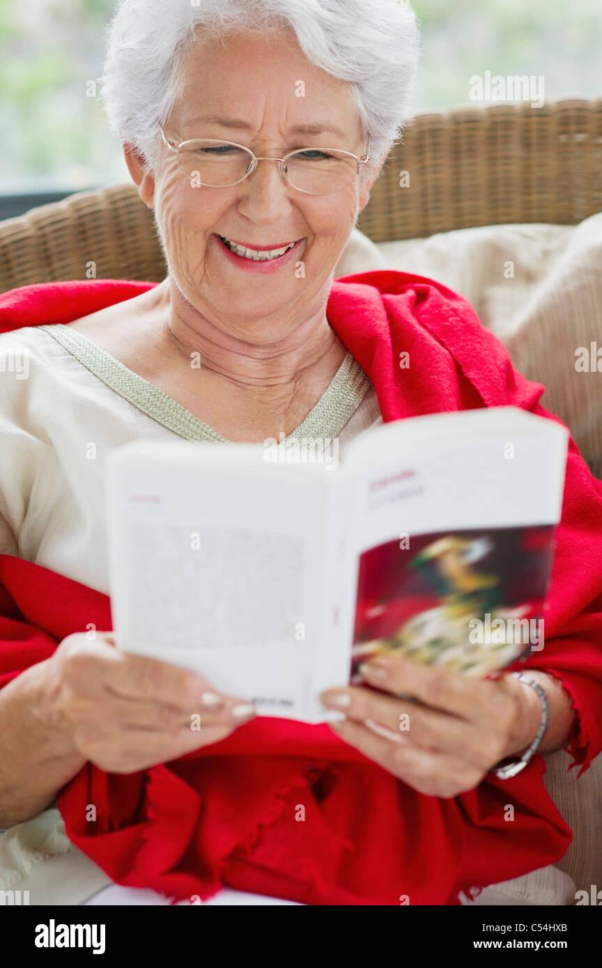 Ältere Frau eine Zeitschrift liest lächelnd Stockfoto