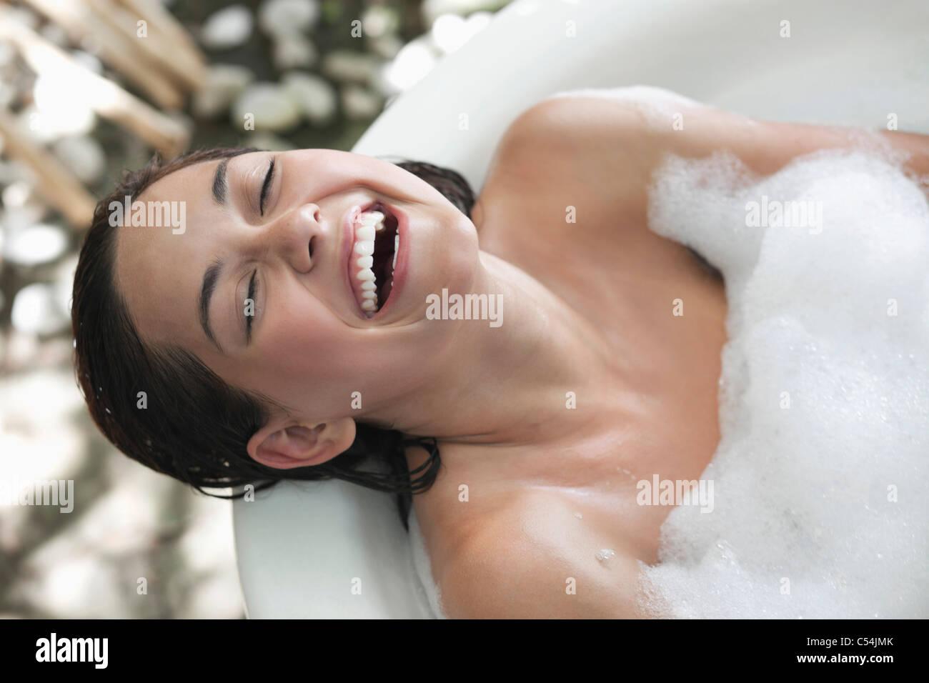 Schöne junge Frau unter Schaumbad und lächelnd Stockbild