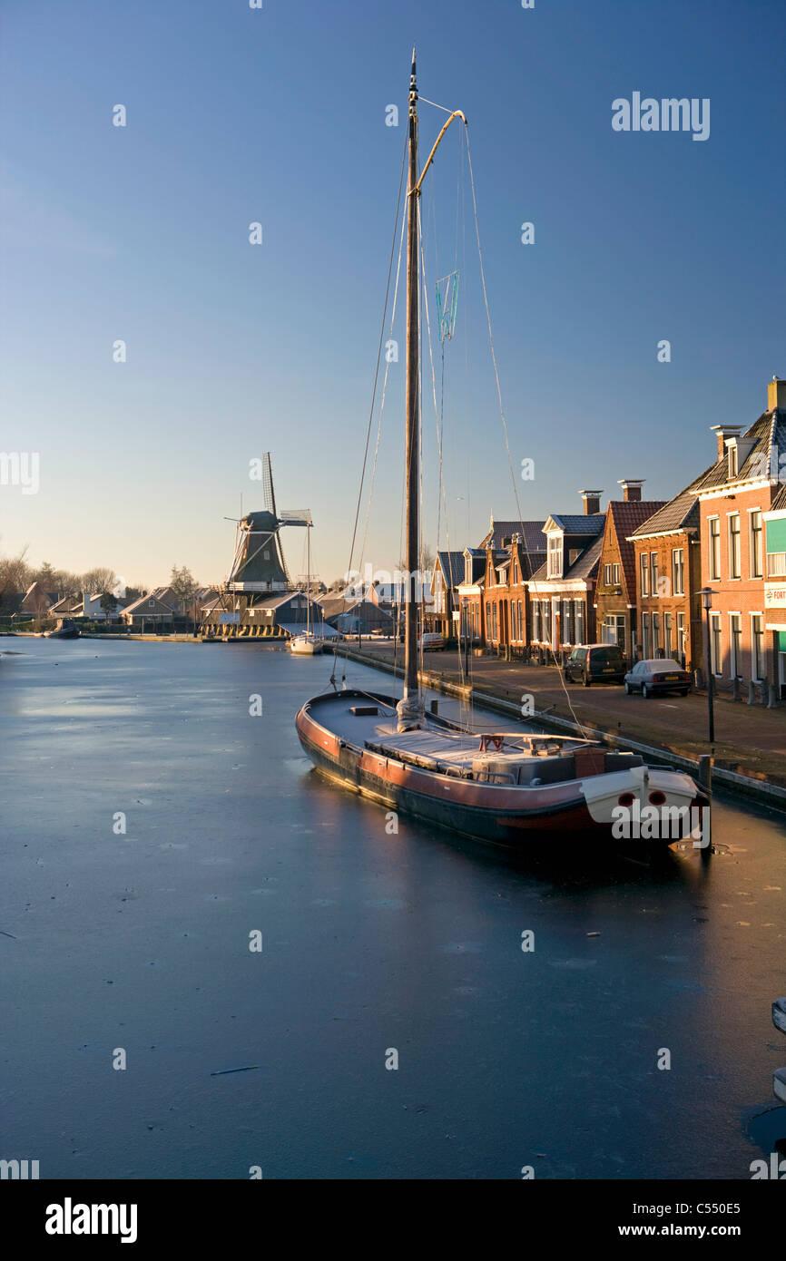Die Niederlande, Woudsend, traditionelle Frachtschiff, jetzt Segelboot für den Tourismus in gefrorenen Kanal. Stockbild