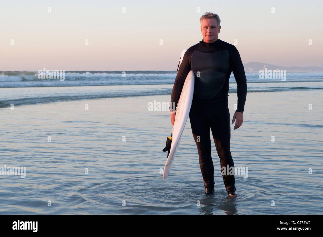 Surfer im Wasser stehend Stockbild