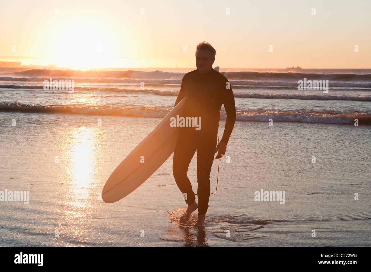 Surfer, die zu Fuß in Wasser Stockbild
