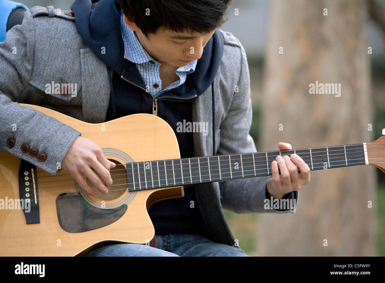 Ein junger Mann, eine Gitarre, draußen spielen Stockbild