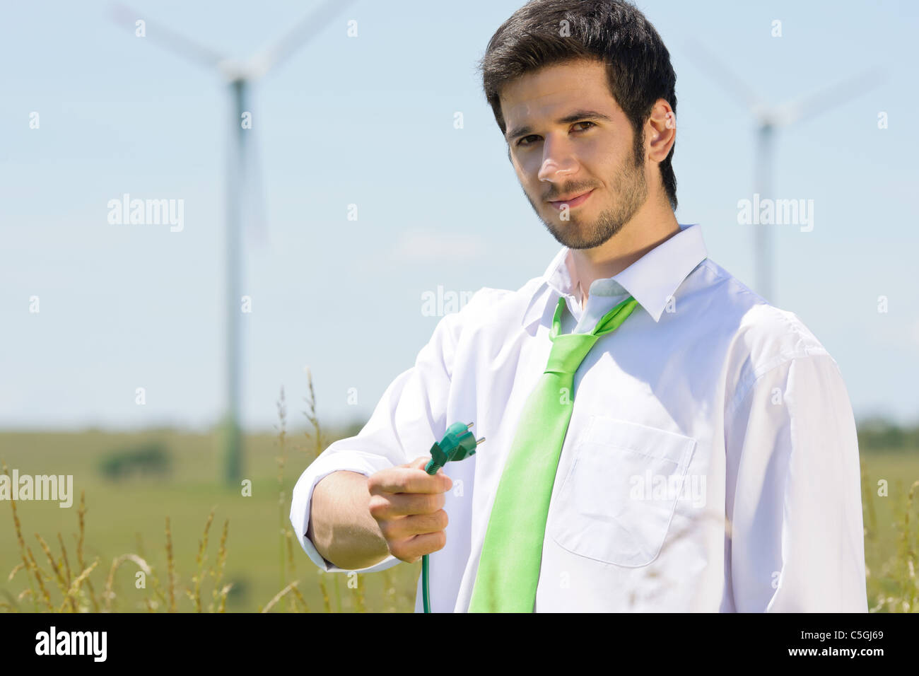 Grüne Energie - Jungunternehmer halten Stecker im Feld mit Windmühle Stockbild
