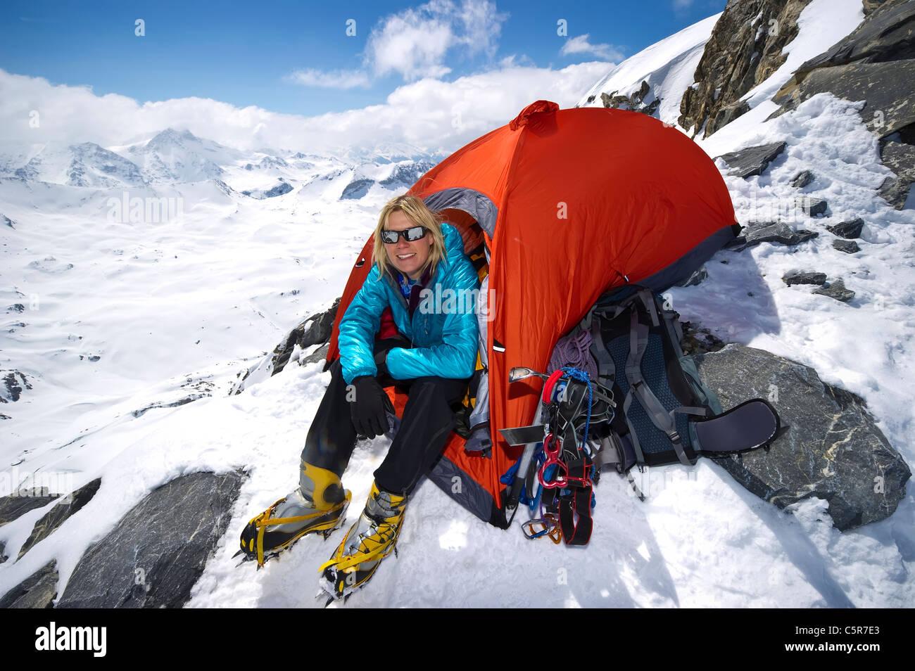 Ein Bergsteiger sitzen im Zelt auf hoch im verschneiten Hochgebirge. Stockbild