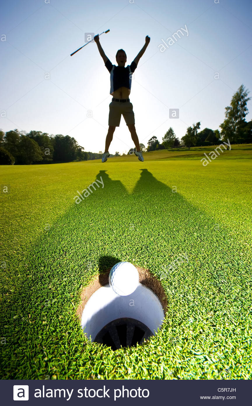 Ein Golfer springt in die Luft, eine gewinnende Put zu feiern. Stockbild