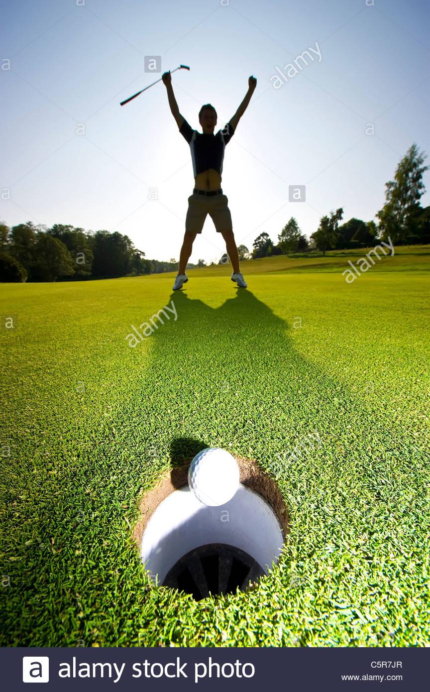 Ein Golfer feiert einen erfolgreichen Put. Stockbild