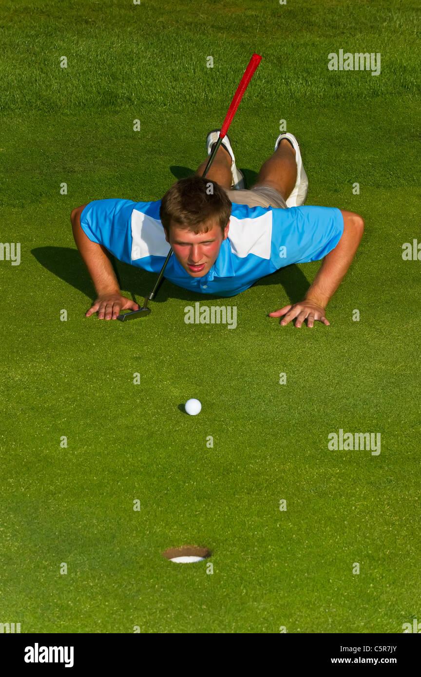 Ein Golfer, Schlange, ein Put auf dem Grün. Stockbild