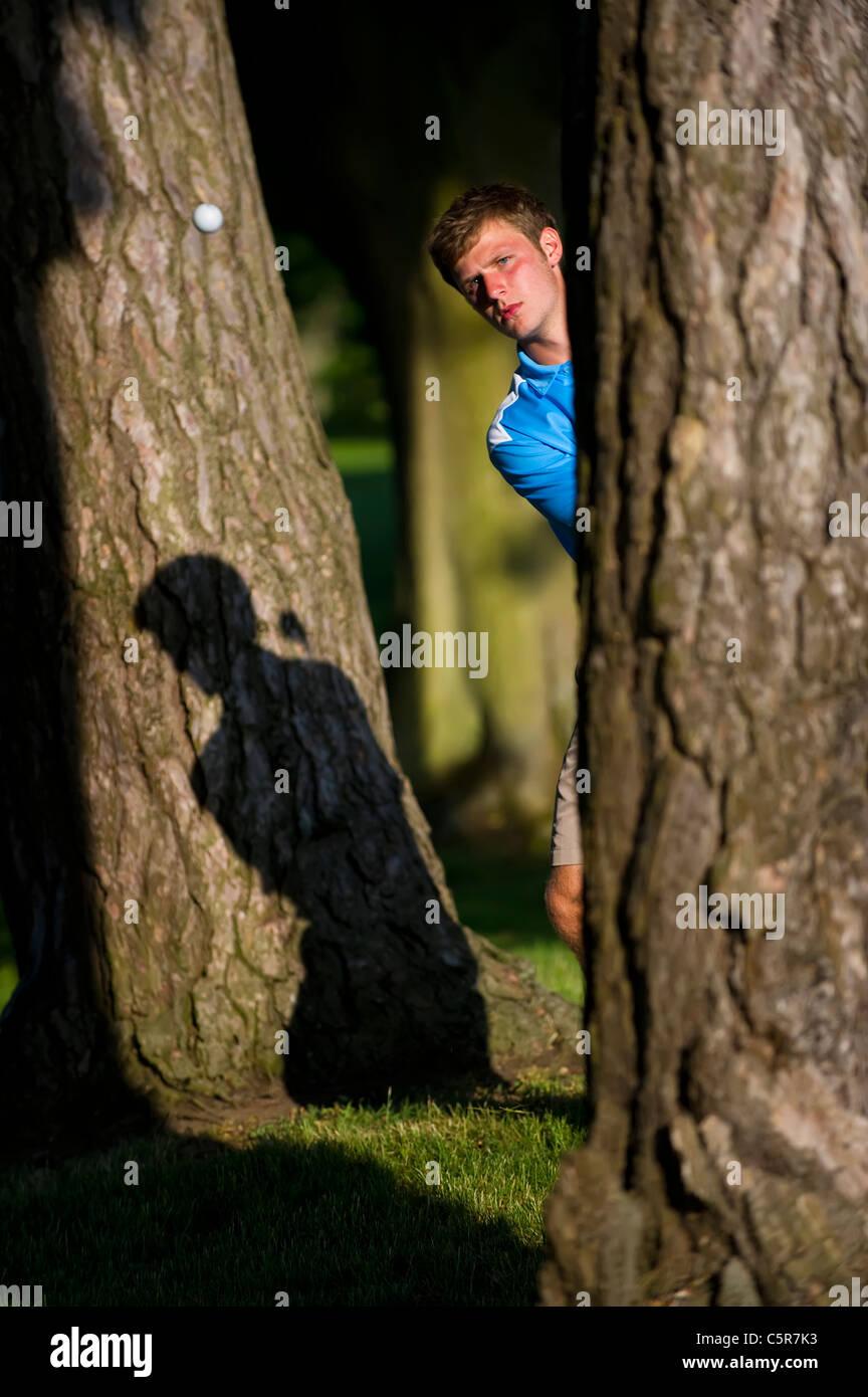 Ein Golfer spielt einen Schuss aus den Bäumen konzentriert am ball. Stockbild