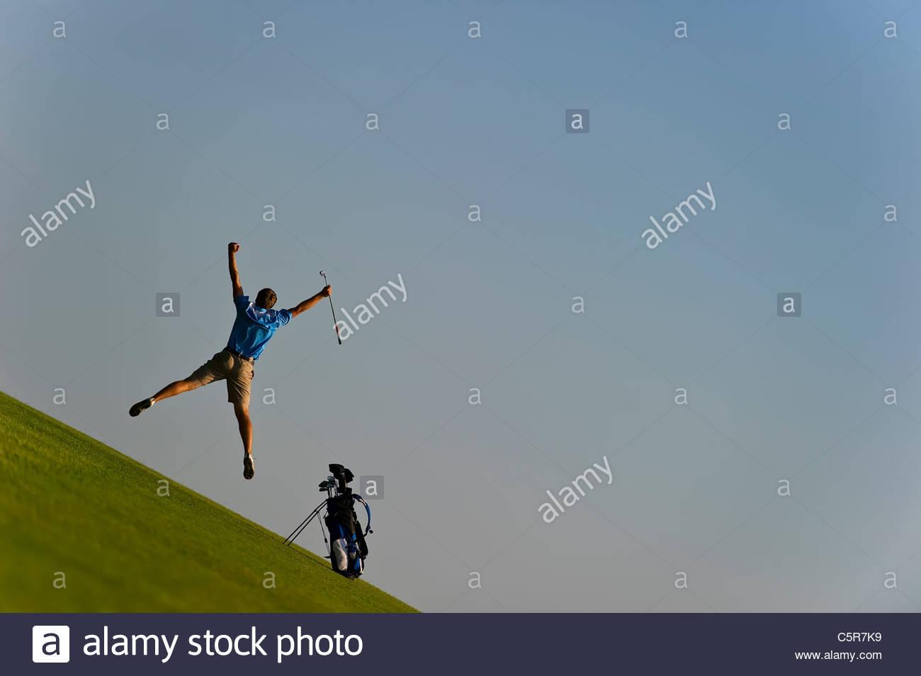 Ein Golfer springt in die Luft zu feiern. Stockbild