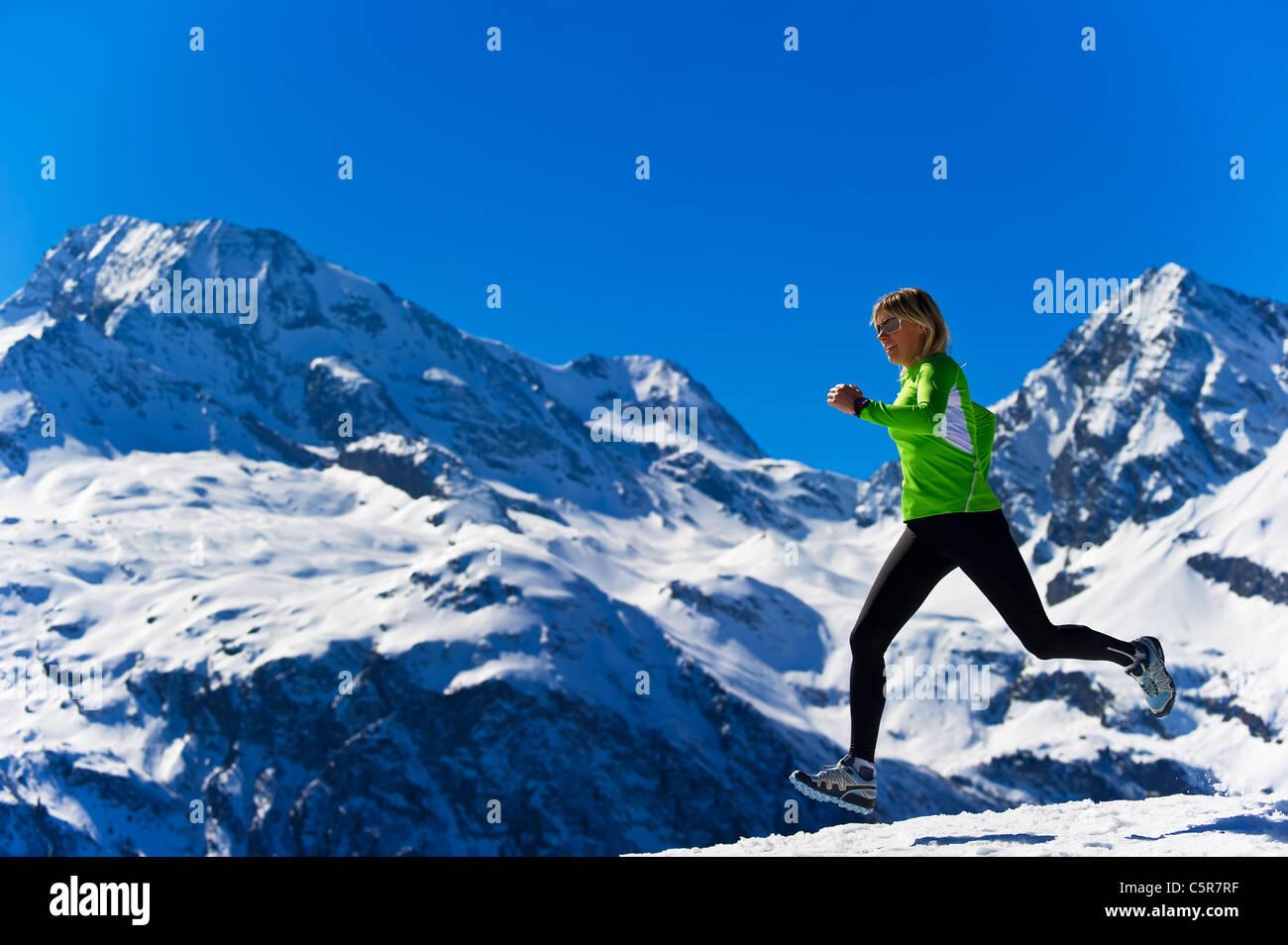 Ein Frauen Joggen über schneebedeckten Alpen. Stockbild